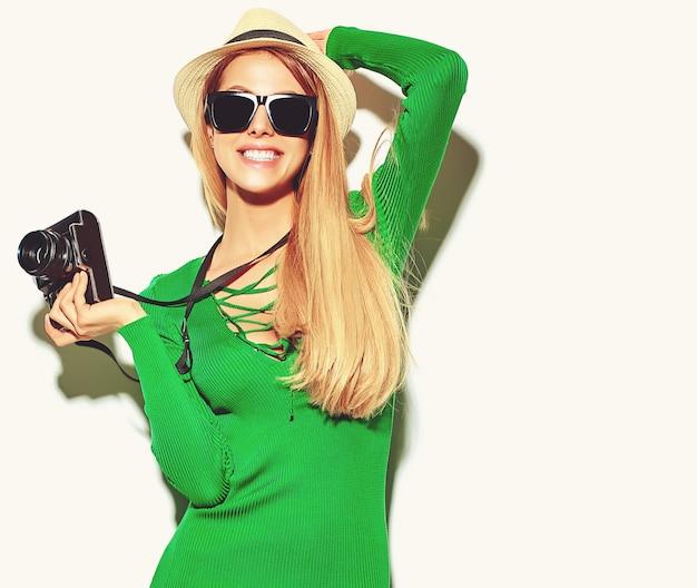 Bella ragazza bionda carina felice donna in abiti casual casual verde estate scatta foto tenendo la macchina fotografica retrò Foto Gratuite