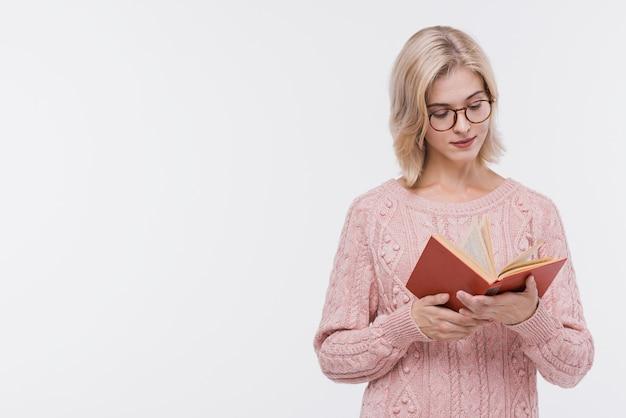 Bella ragazza bionda che legge un libro Foto Gratuite