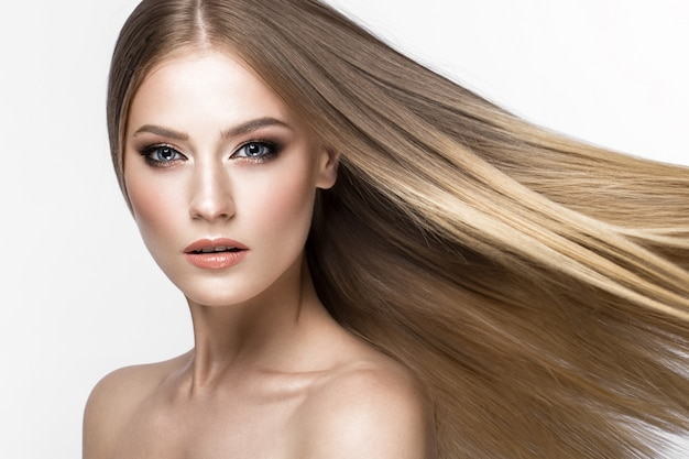 Bella ragazza bionda con capelli perfettamente lisci e trucco classico. Foto Premium