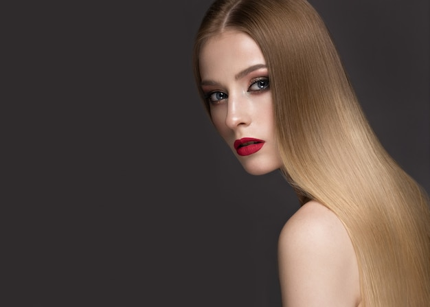 Bella ragazza bionda con capelli perfettamente lisci, trucco classico e labbra rosse. volto di bellezza Foto Premium