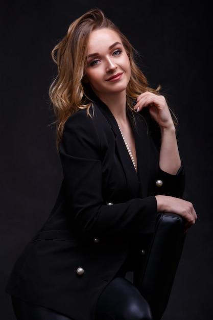 Bella ragazza bionda con il trucco. una ragazza attraente con i capelli lunghi e belli, seduta su una sedia. Foto Premium