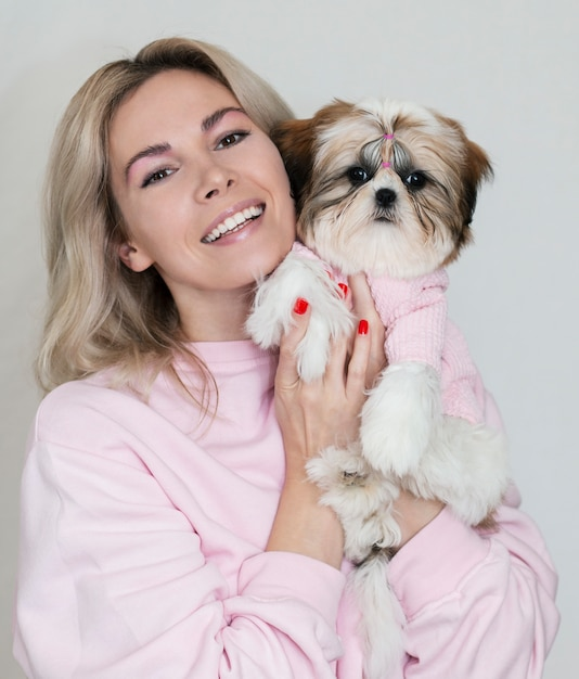 Bella ragazza bionda con un cucciolo carino shih tzu in abiti rosa su sfondo chiaro Foto Premium