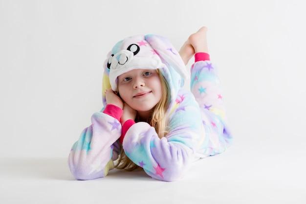 Bella ragazza bionda in posa su bianco in pigiama kigurumi, costume da coniglio Foto Premium