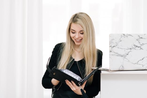 Bella ragazza bionda sorridente con un taccuino e una penna in mano, accanto a un computer portatile su una finestra leggera, impiegato Foto Premium