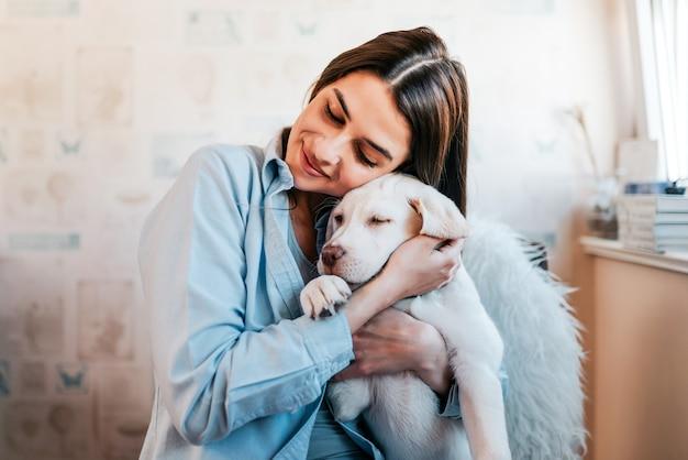 Bella ragazza bruna abbracciando il suo cucciolo a casa. avvicinamento. Foto Premium