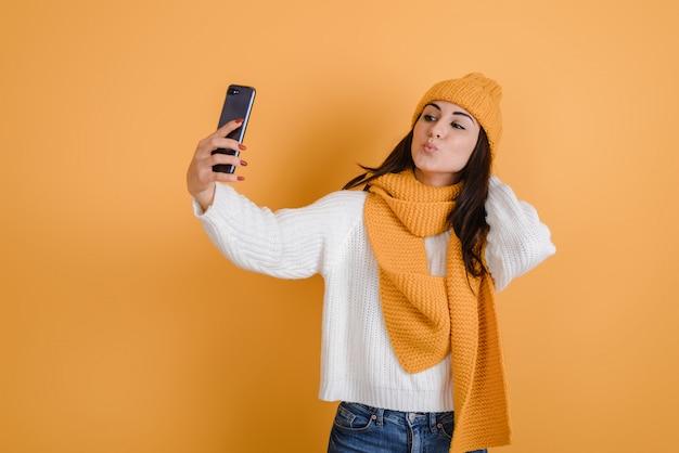 Bella ragazza bruna fa selfie in studio, è in cappello lavorato a maglia e sciarpa Foto Premium