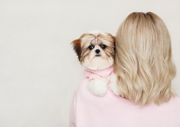 Bella ragazza carina in possesso di un cucciolo di shih tzu ben curato in un maglione rosa sulla sua spalla Foto Premium