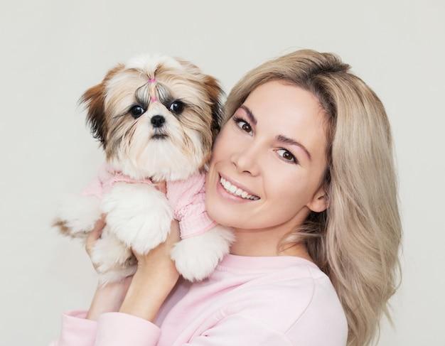 Bella ragazza carina in possesso di un cucciolo di shih tzu ben curato in un maglione rosa Foto Premium