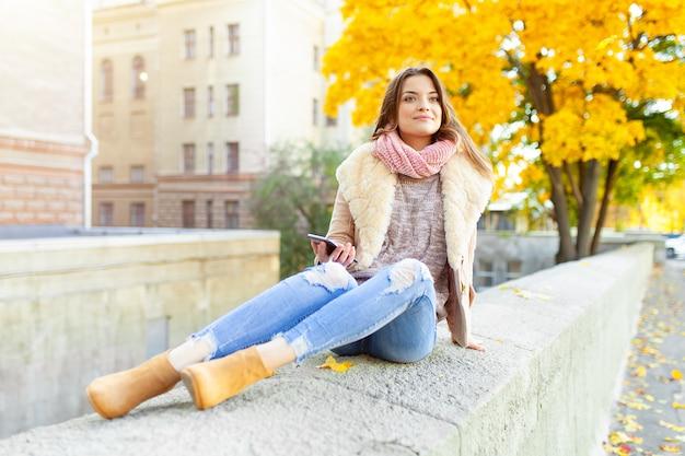 Bella ragazza caucasica del brunette che si siede giorno di autunno caldo con priorità bassa degli alberi con fogliame giallo e una città Foto Premium