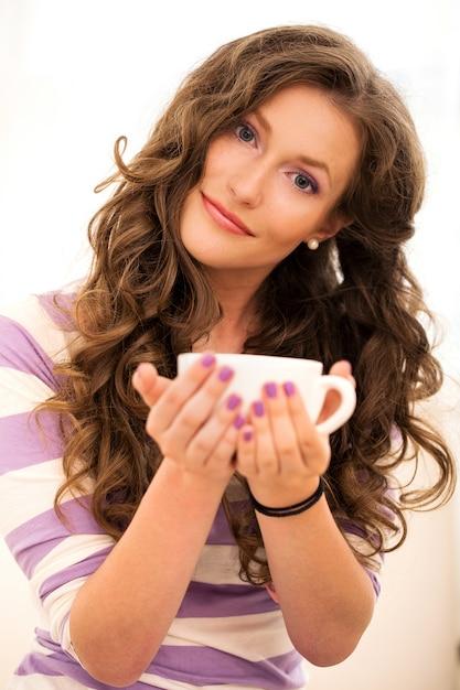 Bella ragazza che beve il caffè Foto Gratuite