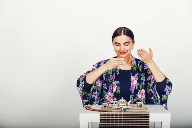 Bella ragazza che beve un tè in uno studio Foto Gratuite