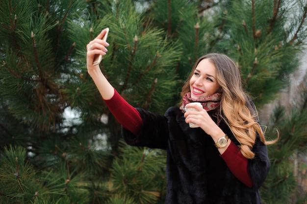 Bella ragazza che fa selfie nel parco di autunno Foto Premium