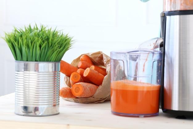 Bella ragazza che produce il succo di carota Foto Gratuite