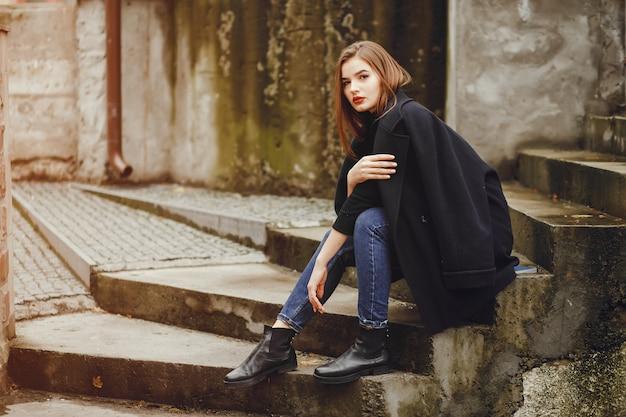 Bella ragazza che si siede in città Foto Gratuite