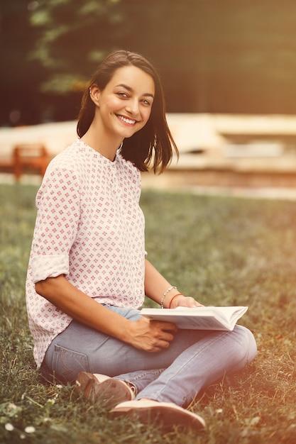 Bella ragazza che tiene un libro aperto Foto Gratuite