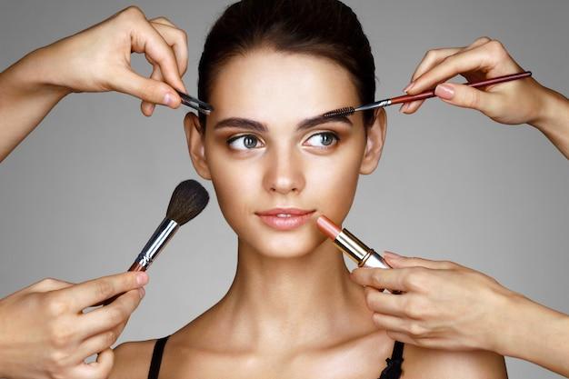 Bella ragazza circondata da mani di truccatori con pennelli e rossetto vicino al viso Foto Premium