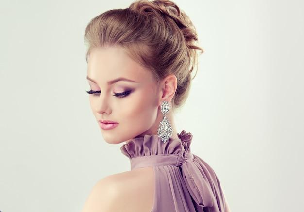 Bella ragazza con acconciatura elegante e grandi orecchini gioielli Foto Premium