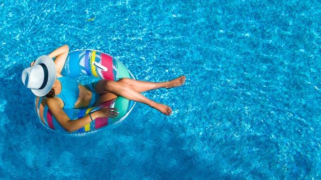 Bella ragazza con cappello in piscina vista aerea dall'alto, la giovane donna si rilassa e nuota sulla ciambella ad anello gonfiabile e si diverte in acqua in vacanza con la famiglia, località di villeggiatura tropicale Foto Premium