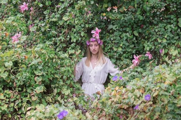 Bella ragazza con corona floreale in posa Foto Gratuite