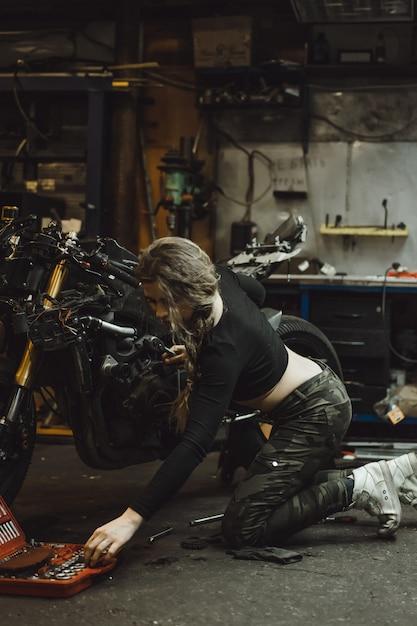 Bella ragazza con i capelli lunghi nel garage di riparare una moto Foto Gratuite