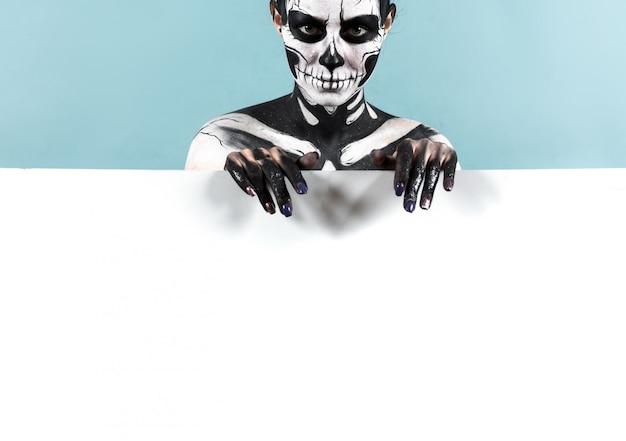 Bella ragazza con il trucco scheletro sopra lo spazio della copia Foto Premium