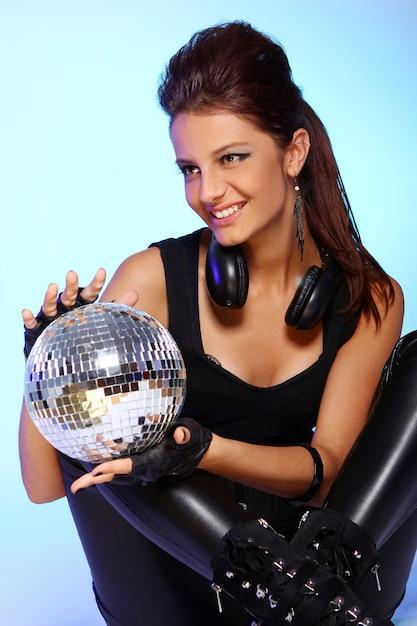 Bella ragazza con le cuffie e la palla da discoteca Foto Gratuite
