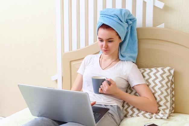 Bella ragazza con un asciugamano in testa, seduta sul letto, lavorando al computer e bere caffè Foto Premium