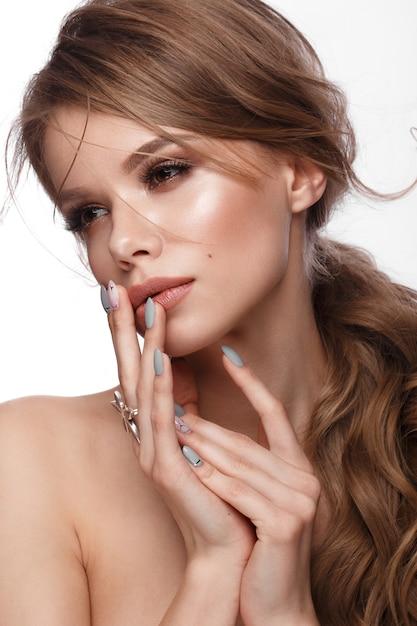 Bella ragazza con un taglio di capelli facile, trucco classico, labbra nude e design per manicure con un barattolo di smalto nelle sue mani, Foto Premium