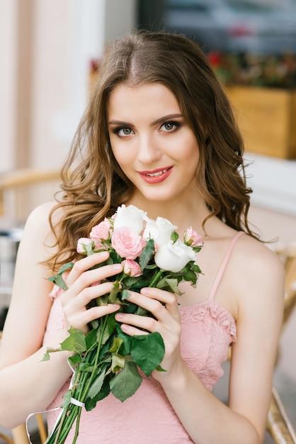 Bella ragazza dai capelli castani con un mazzo di rose, trucco professionale e styling. Foto Premium