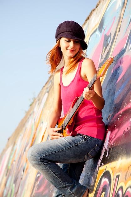 Bella ragazza dai capelli rossi con chitarra e graffiti muro a sfondo. Foto Premium