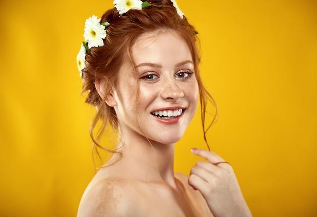 Bella ragazza dai capelli rossi positiva con una corona di camomilla in testa Foto Premium