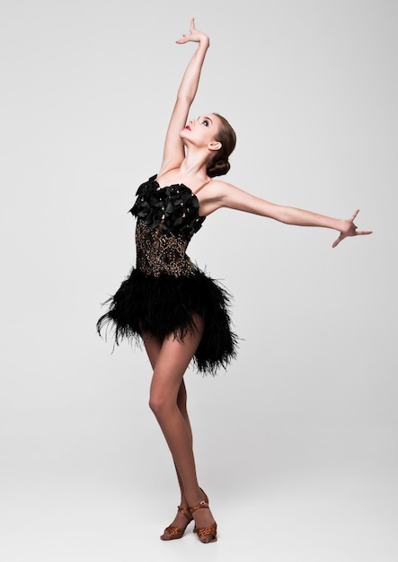 Bella ragazza del ballerino della sala da ballo in vestito elegante dal nero di posa su gray Foto Premium