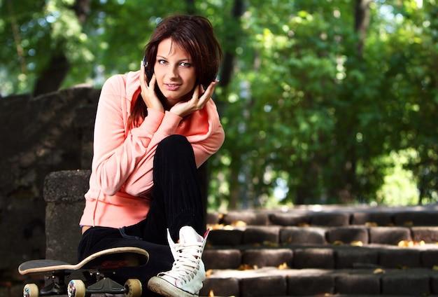Bella ragazza dell'adolescente con le cuffie nel parco Foto Gratuite