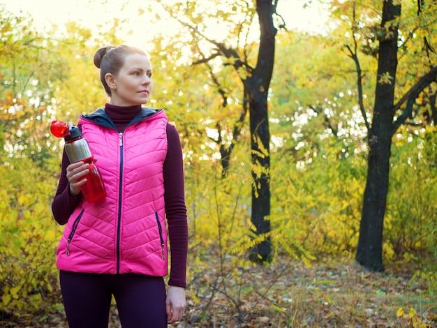 Bella ragazza di sport fitness in abiti sportivi con bottiglia d'acqua sport o bevanda isotonica in mano nella foresta di autunno. Foto Premium