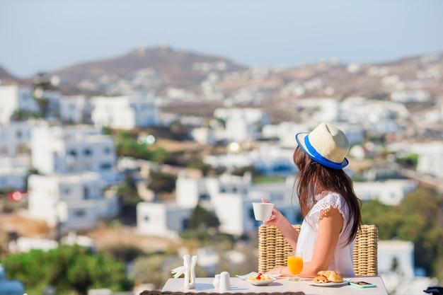Bella ragazza elegante facendo colazione al bar all'aperto con vista mozzafiato sulla città di mykonos. Foto Premium