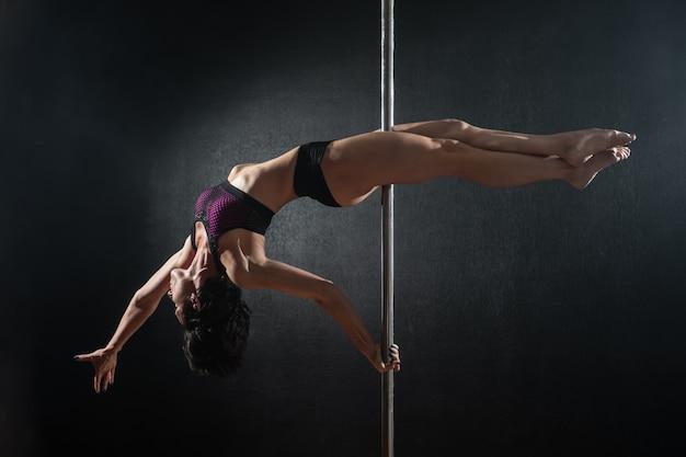 Bella ragazza esile con pilone. ballerino femminile del palo che balla su un fondo nero Foto Premium