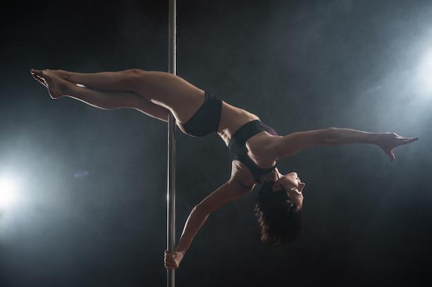 Bella ragazza esile con pilone. ballerino femminile del palo che balla sul nero Foto Premium