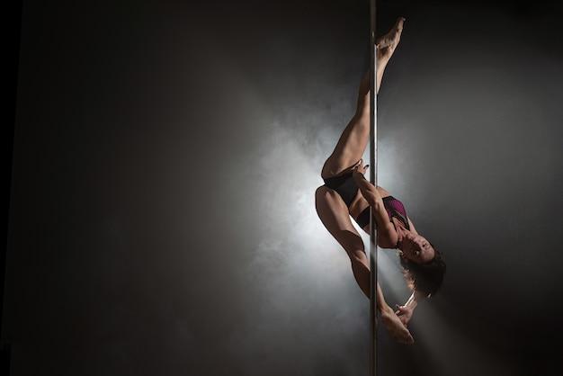 Bella ragazza esile con pilone. danzatrice del palo femminile Foto Premium