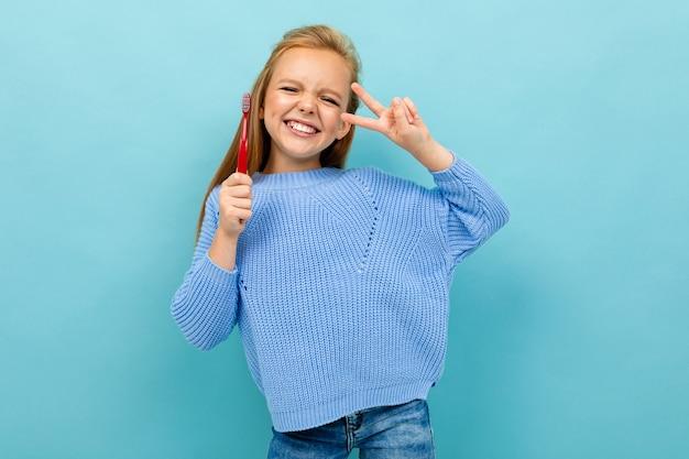 Bella ragazza europea che tiene uno spazzolino da denti in sue mani su blu-chiaro Foto Premium