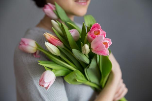 Bella ragazza in abito blu con fiori tulipani nelle mani su uno sfondo chiaro Foto Premium