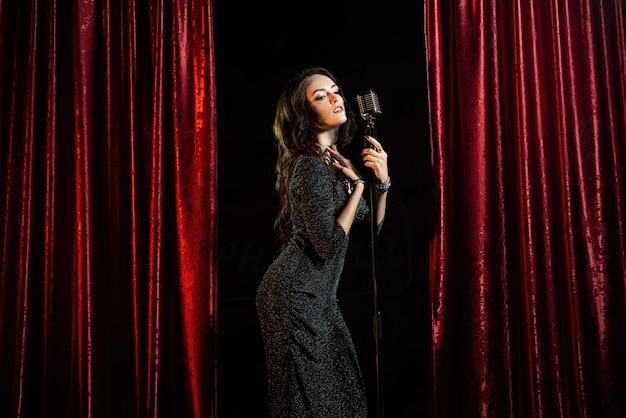 Bella ragazza in abito nero, cantando al microfono nella sala da concerto Foto Premium