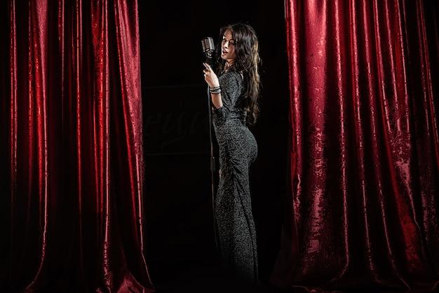Bella ragazza in abito nero, cantando nel microfono nella sala da concerto Foto Premium