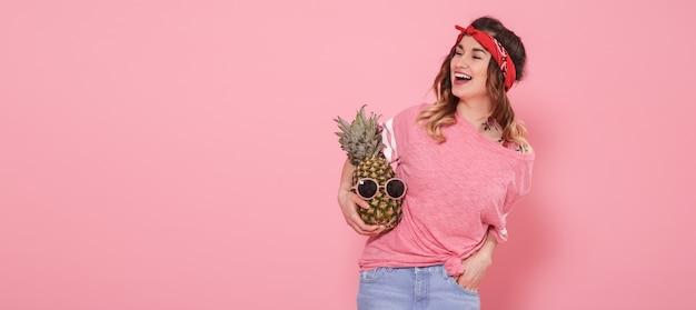Bella ragazza in maglietta rosa, sorridente con ananas sulla parete rosa Foto Gratuite