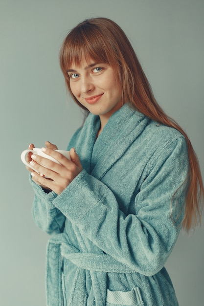 Bella ragazza in piedi in un accappatoio blu Foto Gratuite