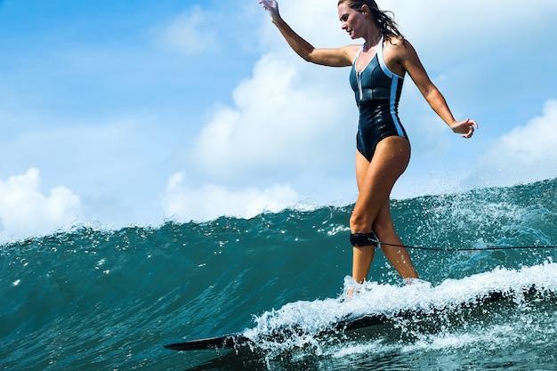 Bella ragazza in sella a una tavola da surf sulle onde Foto Gratuite