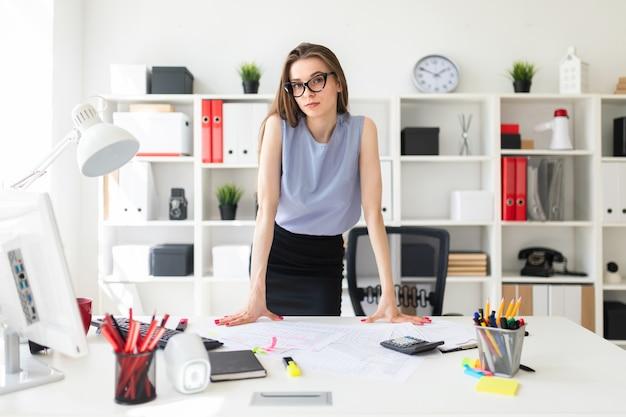 Bella ragazza in ufficio è in piedi vicino al tavolo e ci mette le mani sopra. Foto Premium