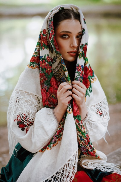 Bella ragazza in un abito etnico tradizionale con un mantello ricamato in testa Foto Gratuite