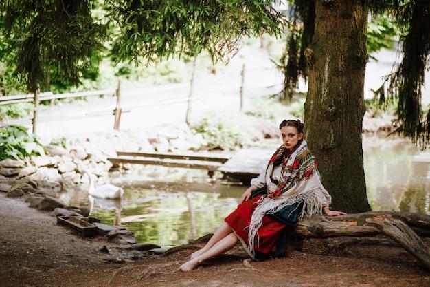 Bella ragazza in un abito ricamato ucraino seduto su una panchina vicino al lago Foto Gratuite