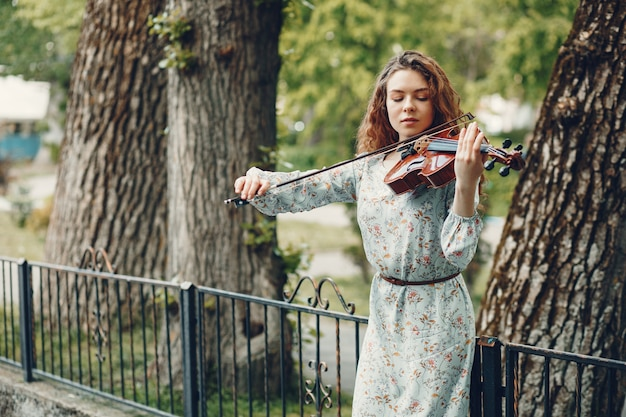 Bella ragazza in un parco estivo con un violino Foto Gratuite