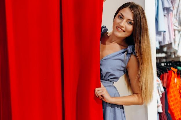 Bella ragazza in vestito blu che prova sui vestiti nel camerino Foto Premium